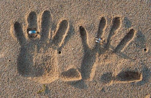 trouwfoto trouwringen in het zand