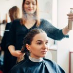 Hairdresser works with hair spray, female client in hairdressing salon. Hairstyle making in beauty studio